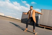bearded businessman in coat riding on penny board