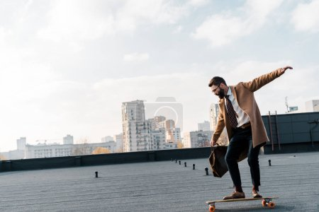 side view of businessman in coat and formalwear riding on penny board