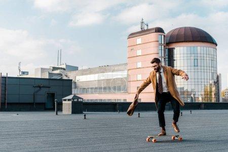 Photo pour Homme d'affaires barbu à cheval sur la planche de penny avec sac dans la main - image libre de droit