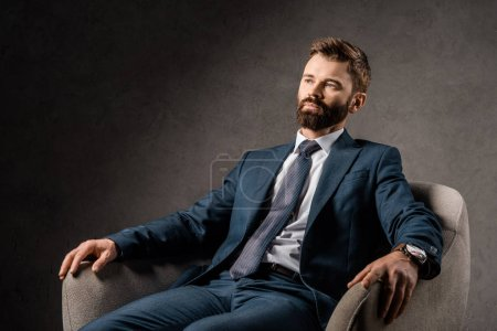 Photo pour Homme d'affaires barbu confiant reposant dans un fauteuil - image libre de droit