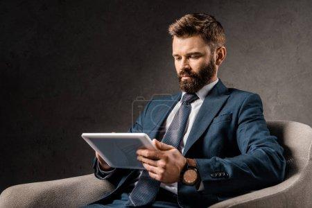 Photo pour Homme d'affaires sérieux utilisant tablette numérique et assis dans le fauteuil - image libre de droit