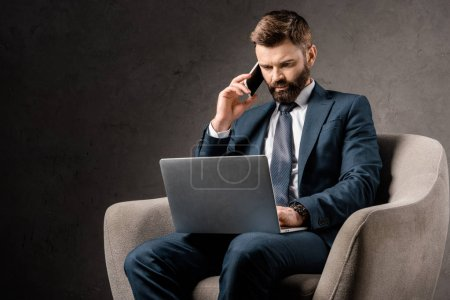 Photo for Confident businessman sitting in armchair with laptop and talking on smartphone - Royalty Free Image