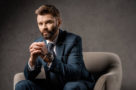 close up of successful businessman sitting in armchair with praying hands