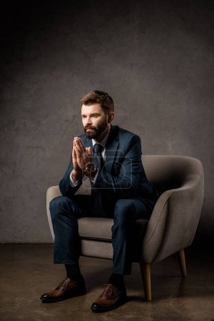 handsome businessman sitting in armchair with praying hands