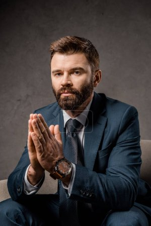 close up of handsome businessman sitting in armchair with praying hands
