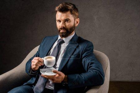 Photo pour Homme d'affaires sérieux montrant une tasse blanche avec café assis dans le fauteuil - image libre de droit