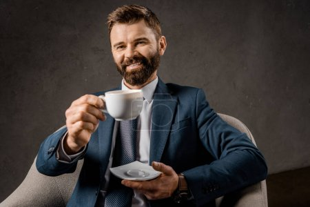 Photo for Cheerful bearded businessman showing cup of coffee - Royalty Free Image