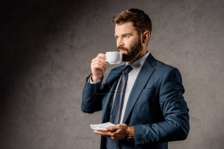 handsome businessman drinking coffee and holding saucer