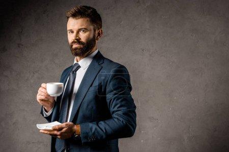 Photo pour Bel homme d'affaires debout avec une tasse de café - image libre de droit
