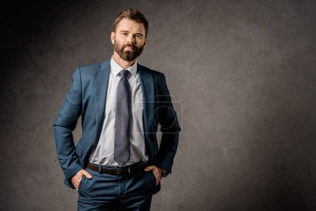 handsome bearded businessman standing in formalwear with hands in pockets