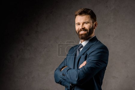 Photo for Smiling bearded businessman standing with crossed arms - Royalty Free Image