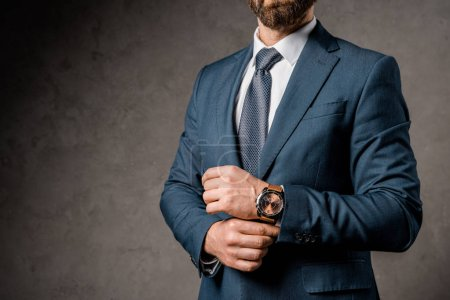 Photo pour Recadrée vue d'homme d'affaires en vetu avec montre sur place - image libre de droit