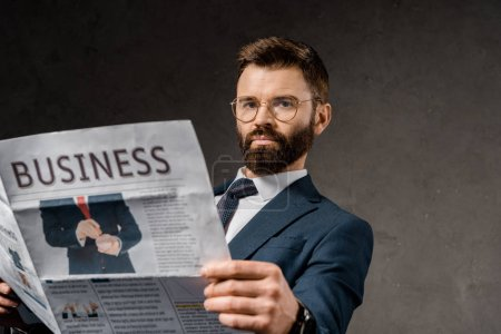 Photo for Bearded businessman in formalwear holding newspaper - Royalty Free Image