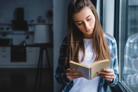 Photo pour Belle jeune femme en chemise à carreaux debout près de la fenêtre et le livre de lecture - image libre de droit