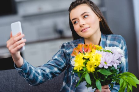 beautiful smiling young woman holding flowers and taking selfie with smartphone at home