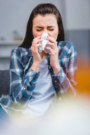 selective focus of young woman with allergy blowing nose in facial tissue