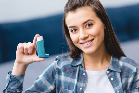happy young woman holding inhaler and smiling at camera