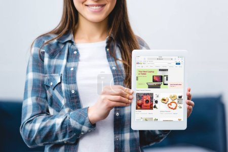 Photo for Cropped shot of smiling girl holding digital tablet with ebay app - Royalty Free Image
