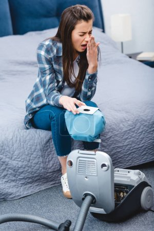 high angle view of girl with allergy holding container from vacuum cleaner with dust and sneezing in bedroom
