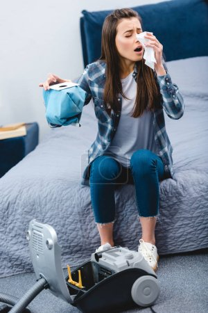 Photo for Girl with allergy holding container from vacuum cleaner with dust and sneezing in bedroom - Royalty Free Image