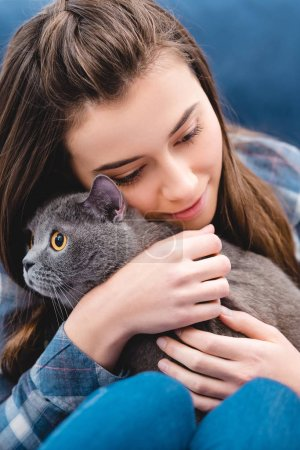 Photo pour Vue rapprochée du chat d'adorables british shorthair hugging jeune fille à la maison - image libre de droit
