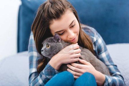 Photo pour Chat d'adorables british shorthair hugging jeune fille dans la chambre - image libre de droit
