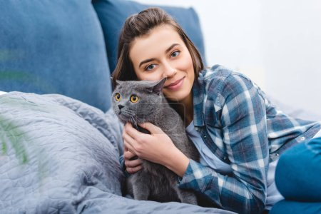 happy girl hugging cute grey cat and smiling at camera in bedroom