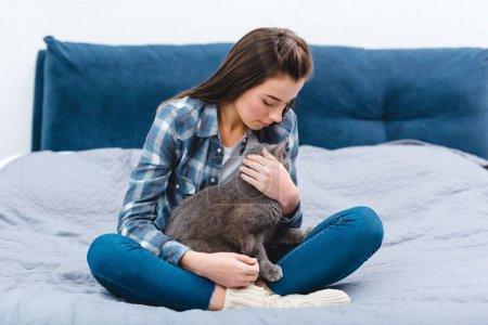Photo pour Belle jeune femme assise sur le lit avec chat mignon british shorthair - image libre de droit