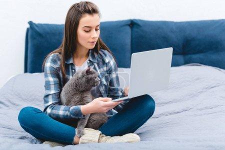 Photo pour Jeune femme à l'aide d'ordinateur portable tout en étant assis sur le lit avec chat mignon british shorthair - image libre de droit