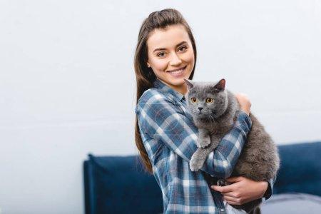 Photo pour Fille tenue british shorthair chat et souriant à la caméra - image libre de droit