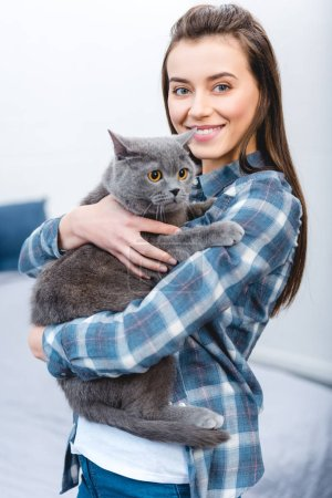 Photo pour Belle jeune femme tenant british shorthair chat et souriant à la caméra - image libre de droit