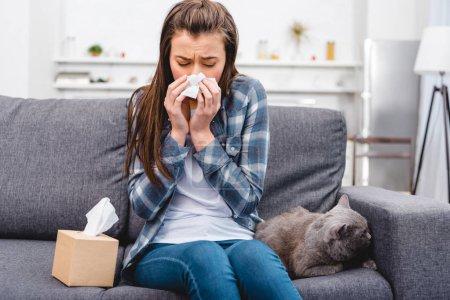 Photo pour Fille souffler le nez dans le tissu facial tout en étant assis avec chat sur le canapé - image libre de droit