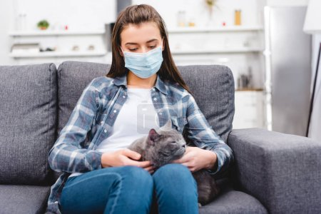 girl in medical mask holding cat and suffering from allergy at home