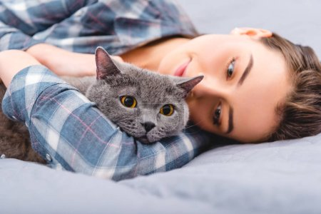 Photo pour Belle fille heureuse couché sur le lit avec chat british shorthair - image libre de droit