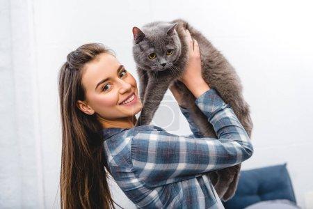 Photo pour Heureuse jeune femme tenant british shorthair chat et souriant à la caméra - image libre de droit