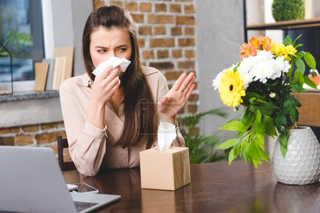young businesswoman blowing nose and looking at flowers while suffering from allergy at workplace