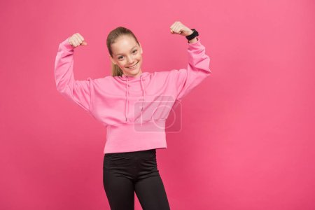 Photo for Strong youngster showing muscles and biceps, isolated on pink - Royalty Free Image