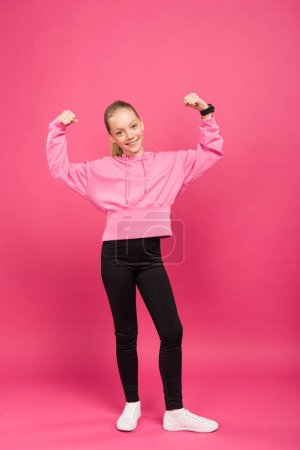 Photo for Strong athletic kid showing muscles and biceps, isolated on pink - Royalty Free Image