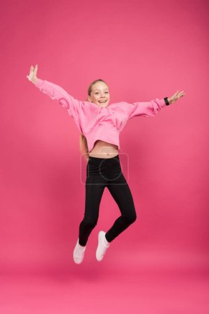 Photo for Happy blonde child jumping isolated on pink - Royalty Free Image
