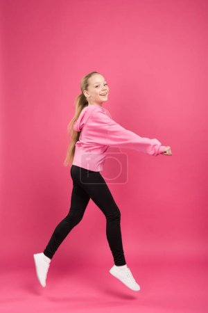 adorable blonde child dancing isolated on pink