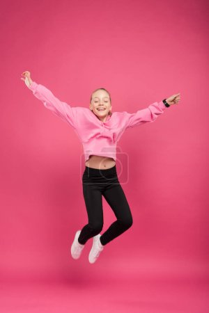 Photo for Adorable cheerful kid jumping isolated on pink - Royalty Free Image