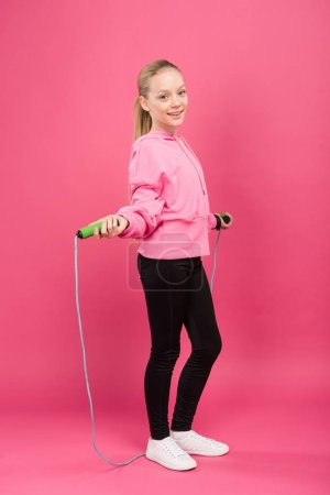 Photo for Happy child in sportswear training with skipping rope, isolated on pink - Royalty Free Image