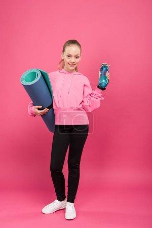 Photo pour Adorable enfant tenant tapis de fitness et bouteille de sport avec de l'eau, isolé sur rose - image libre de droit