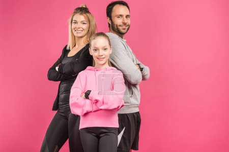 Photo for Athletic family posing in sportswear with crossed arms, isolated on pink - Royalty Free Image