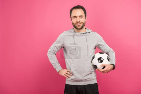 handsome football player holding ball isolated on pink