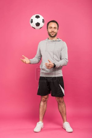 Photo for Nale football player throwing up ball isolated on pink - Royalty Free Image