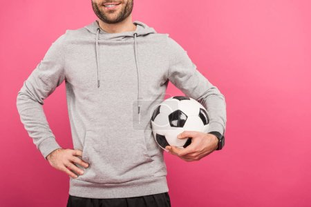 cropped view of football player holding ball isolated on pink