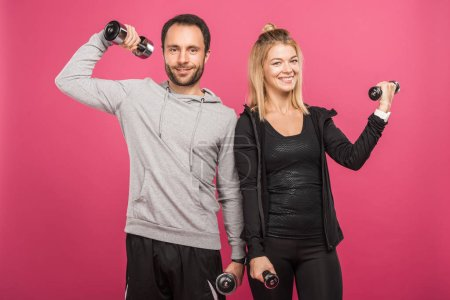 Photo for Athletic couple training with dumbbells, isolated on pink - Royalty Free Image