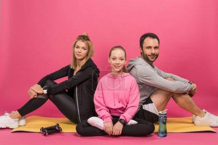Photo pour Famille athlétique assis sur tapis de fitness avec haltères et bouteille de sport, isolé sur rose - image libre de droit