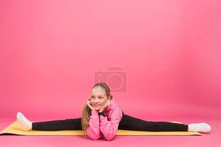 Photo pour Adorable jeune faisant split sur tapis de fitness, isolé sur rose - image libre de droit